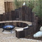 SARAH'S ATTRACTIVE GARDEN WITH CURVED RAILWAY SLEEPER BENCH AND RAISED BEDS