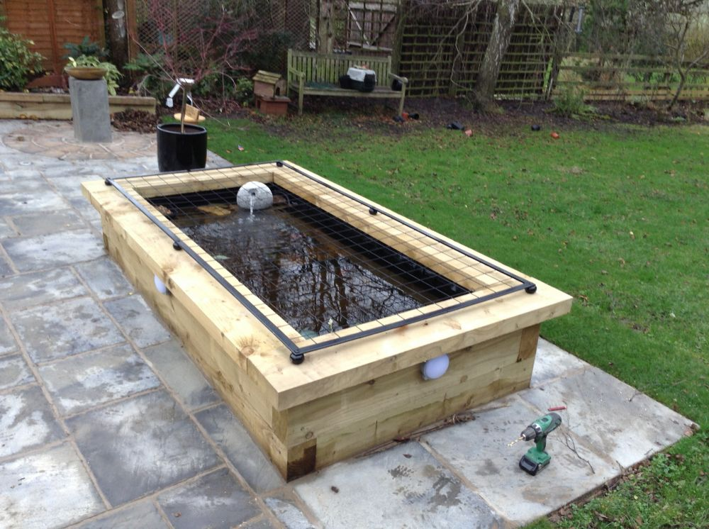 Raised pond with new railway sleepers for Raised koi pond ideas