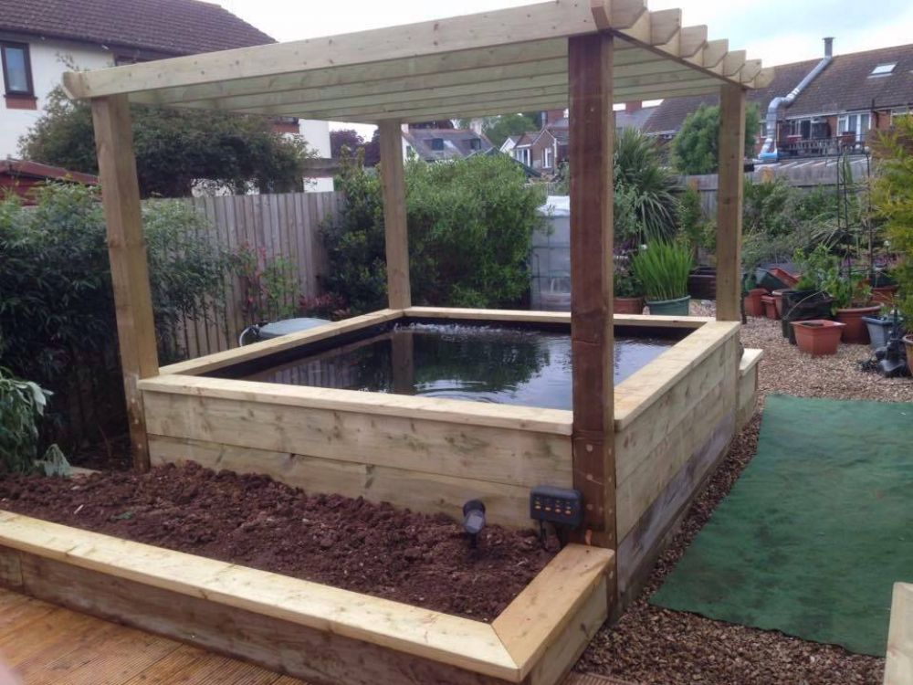 Railway sleeper pond pergola and raised beds for Raised koi pond ideas