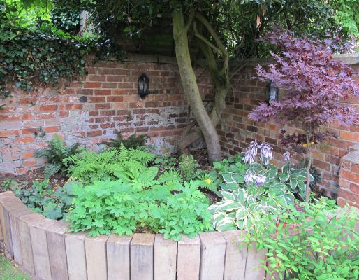The Old Bakehouse's curved retaining wall from reclaimed oak railway sleepers