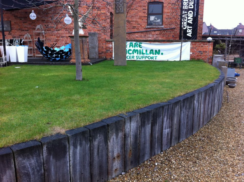 Raised beds and retaining walls with new and used railway for Garden railway designs